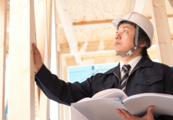 男の人が建物の骨組みを検査している写真